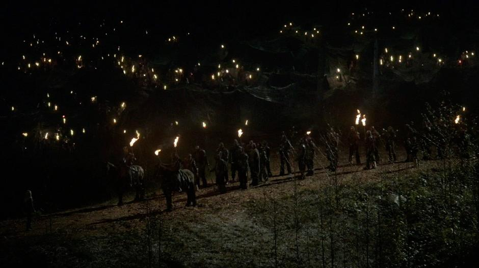 Clarke walks up to a large group of Grounders who are waiting on the path to the camp.