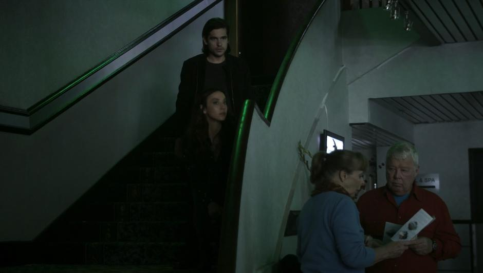 Julia & Quentin crouch on the stairs while Richard makes a distraction in the lobby.