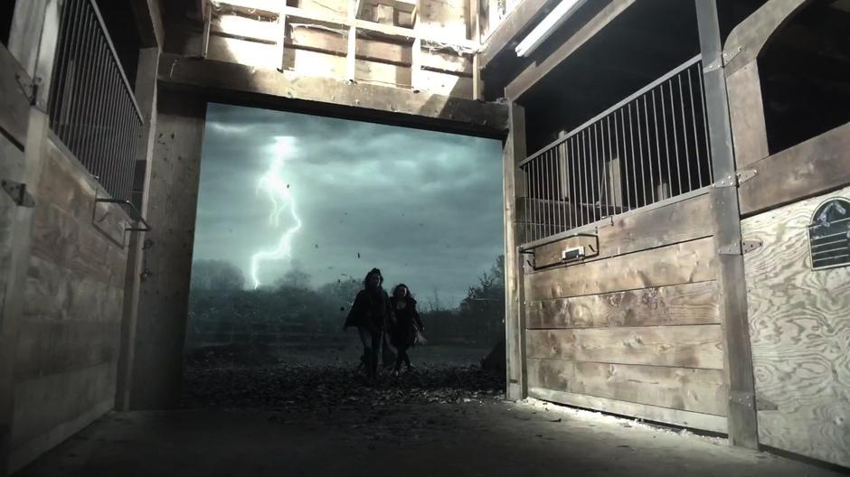 Kady and Julia run into the bar while lightning hits the ground behind them.