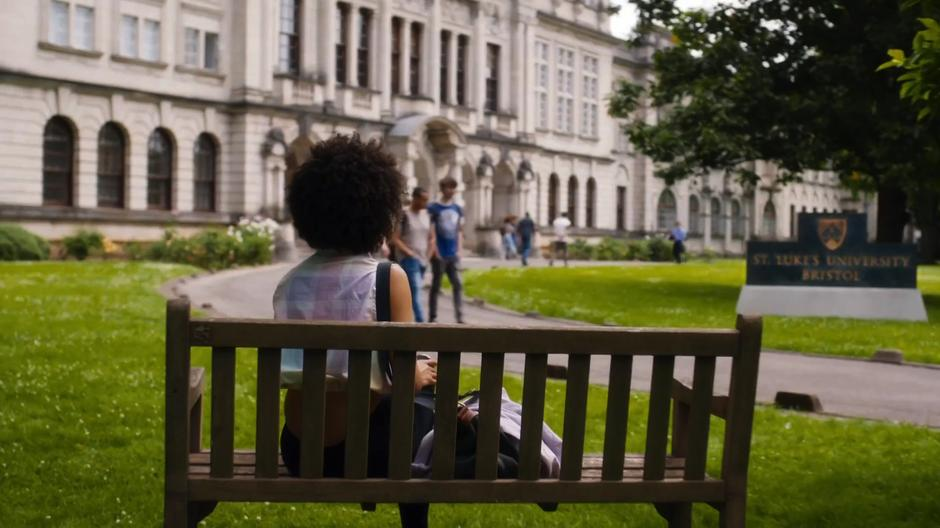 Bill sits on a bench in front of the university waiting for her time to meet with the Doctor.