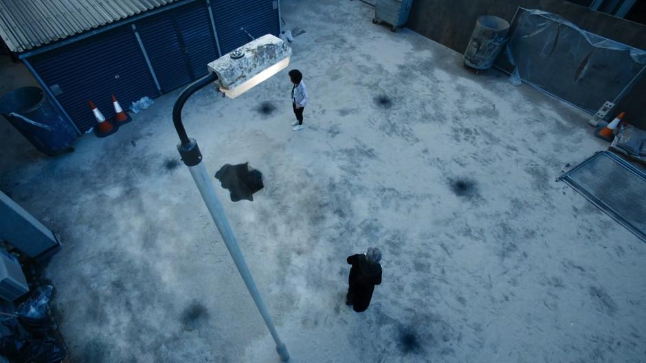 Bill and the Doctor look around the courtyard at the five small burn marks surrounding the strange puddle.