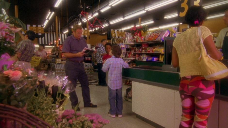 Shawn asks for more money to buy an extra candy bar from his father while Gus stands with his own supply.