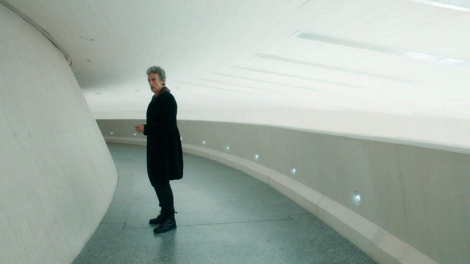 The Doctor looks down a curved corridor where an emoji-bot is waiting.