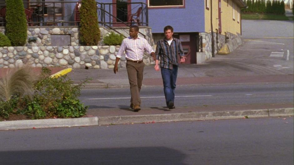 Gus and Shawn walk across the street towards the tanning salon and Shawn explains why he believes this is the correct place to investigate.