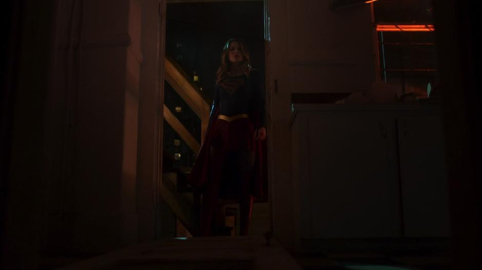 Kara kicks down the door to the house and looks inside.
