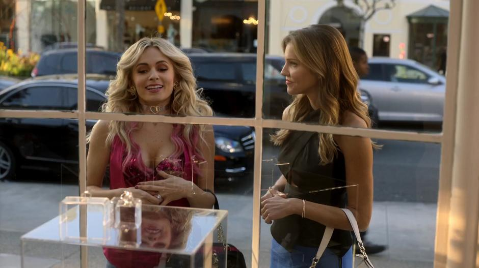 Candy looks at rings in the window display while Charlotte watches her.