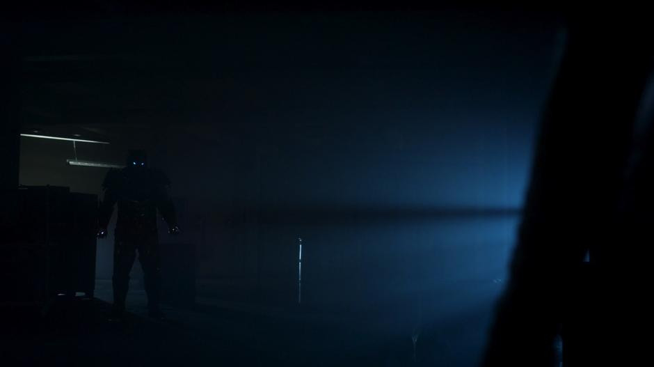 Savitar approaches Caitlin in the darkened interior of the warehouse.