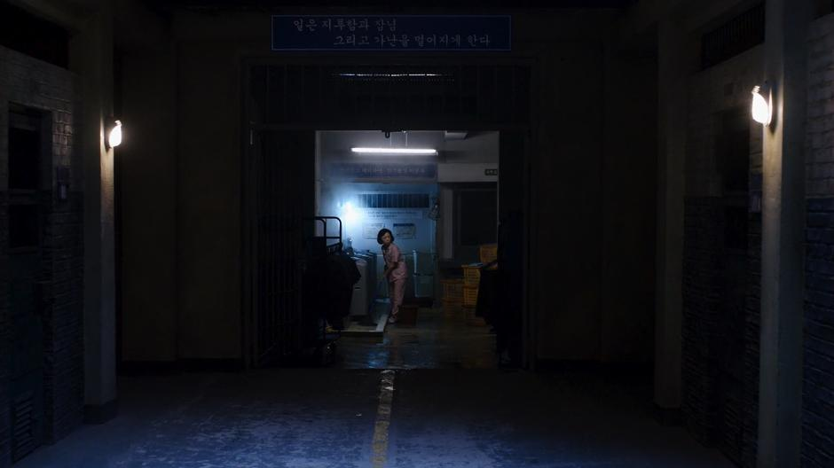 Min-Jung looks up from where she is mopping at the end of the hall after Sun is escorted past.