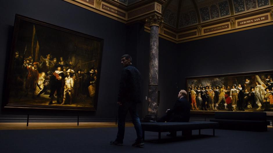 Will looks around the space before sitting down on the bench with Chroome in front of Rembrandt's The Night Watch.