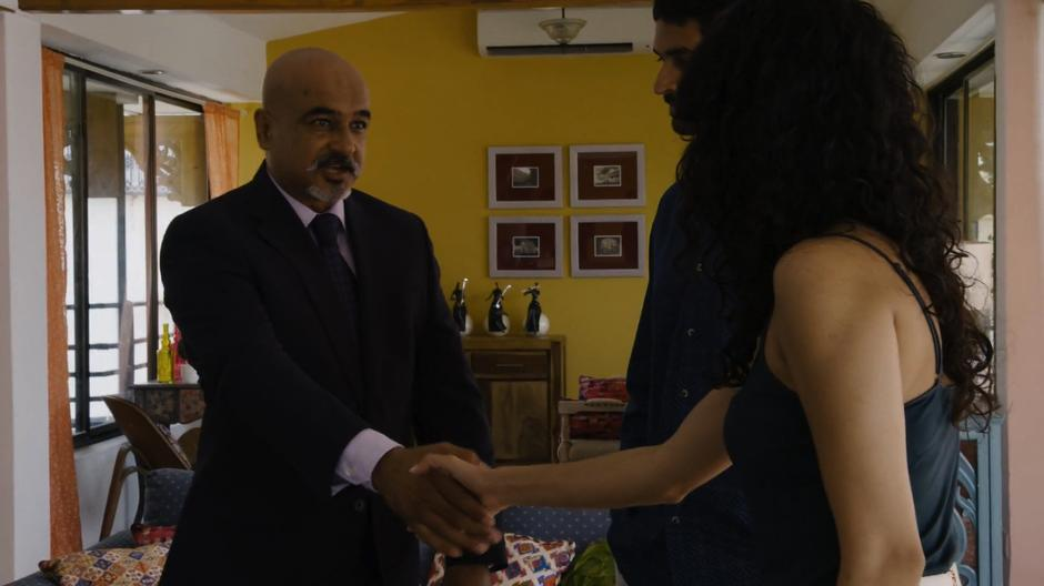 Kala shakes hands with the government agent after Rajan has introduced them.
