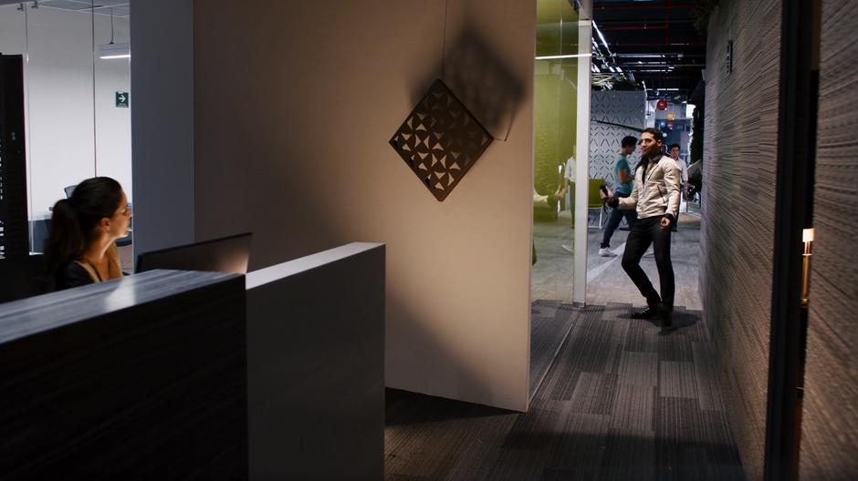 Lito dances down the hallway towards his agent's office while his agent's assistant looks over concerned.