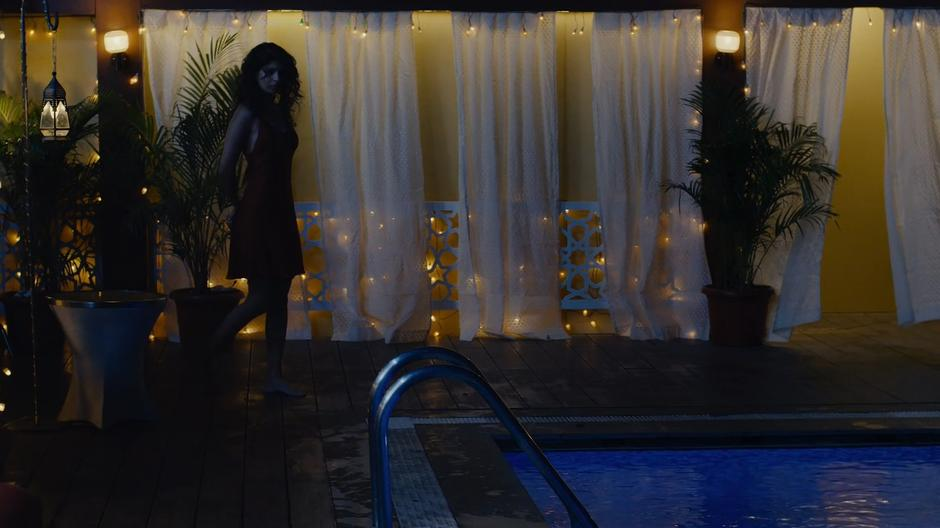 Kala walks up to the edge of her rooftop pool at night.