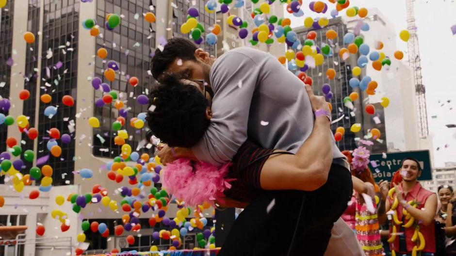 Lito dips Hernando down for a kiss while they are surrounded by balloons and confetti.