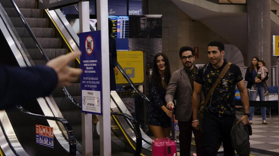 Lito, Hernando, and Dani step off the escalator and approach the waiting fans.