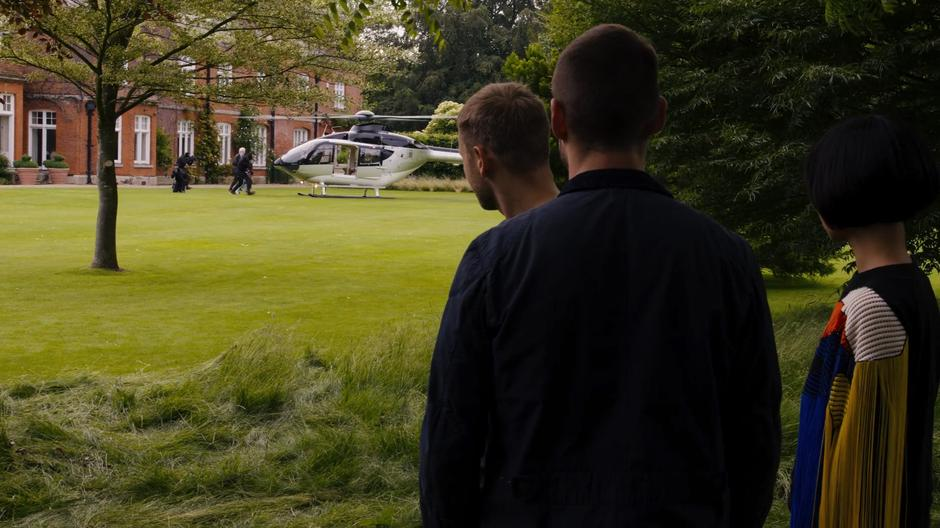 Wolfgang, Will, and Sun watch as Whispers and his family are bundled into a waiting helicopter by several armed guards.