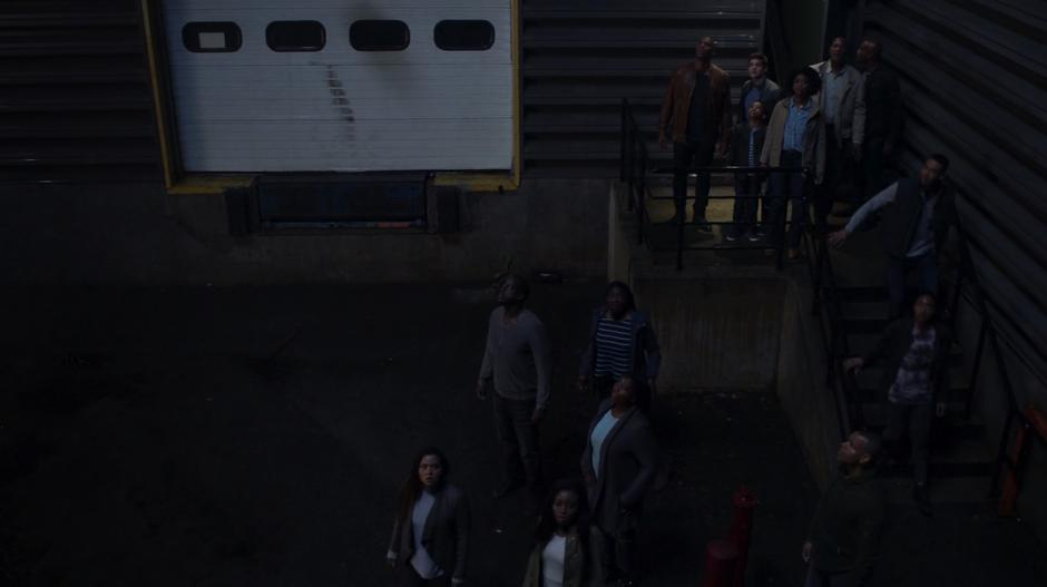 James, Winn, Marcus, Erika, and the other aliens look up into the sky outside the warehouse.