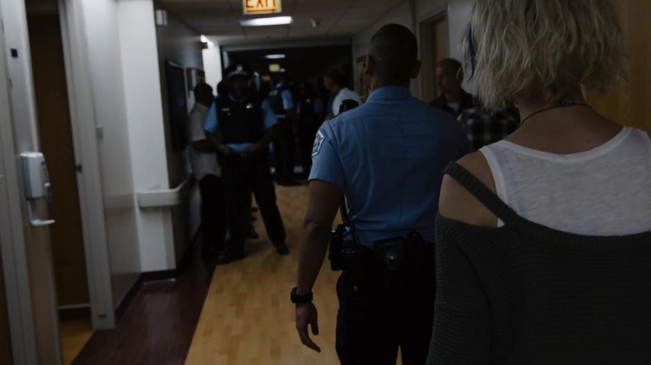 Diego walks down the hospital corridor with Riley following through the assembled police officers.
