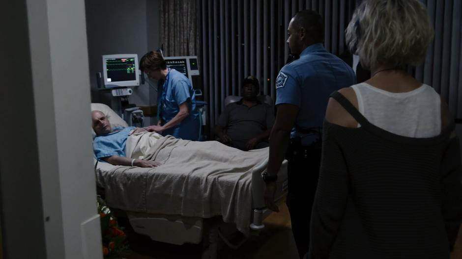 Diego and Riley enter the hospital room where Michael is lying on the bed being attended to by a nurse.