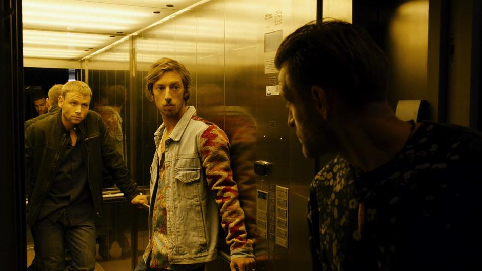 Wolfgang and Felix look out of the elevator as they are ushered in by Sebastian Fuchs's guard.