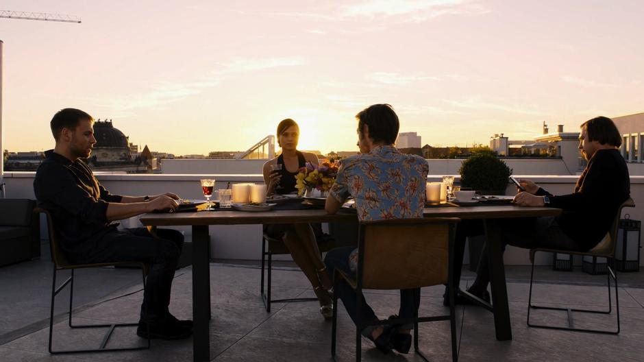 Wolfgang, Lila, Felix, and Sebastian sit at the table talking in front of the sunset after finishing their meal.