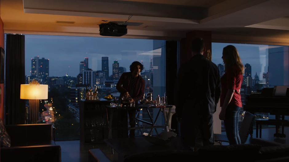 Jonas pours himself a drink in front of the London skyline while explaining his surprise survival to Will and Nomi.