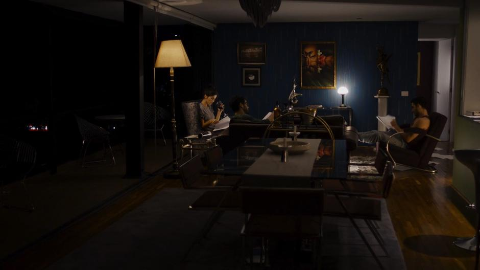 Dani, Hernando, and Lito sit in the living room at night reading through the scripts.