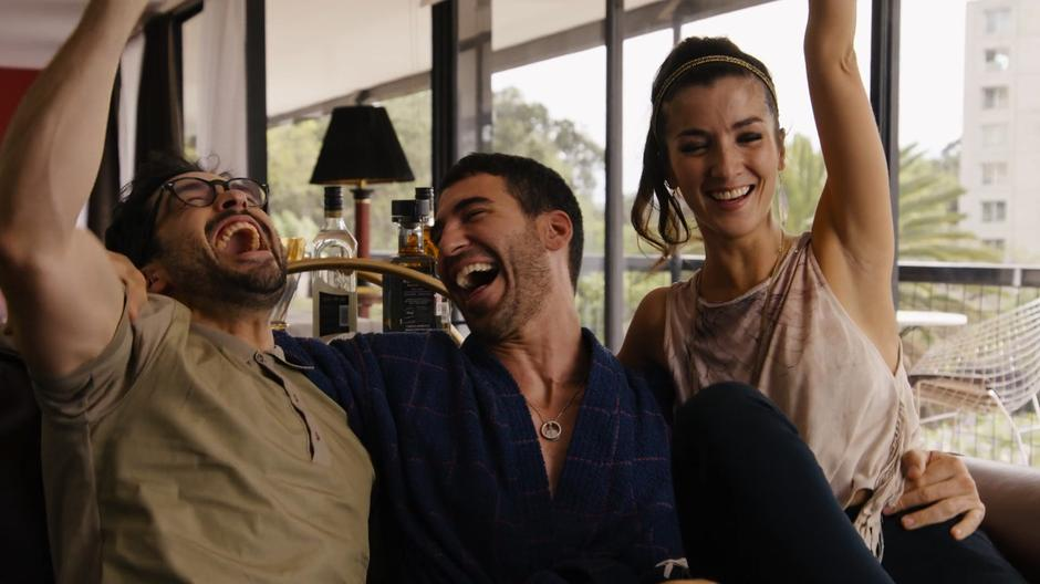 Hernando, Lito, and Dani celebrate after Dani lands Lito the meeting.