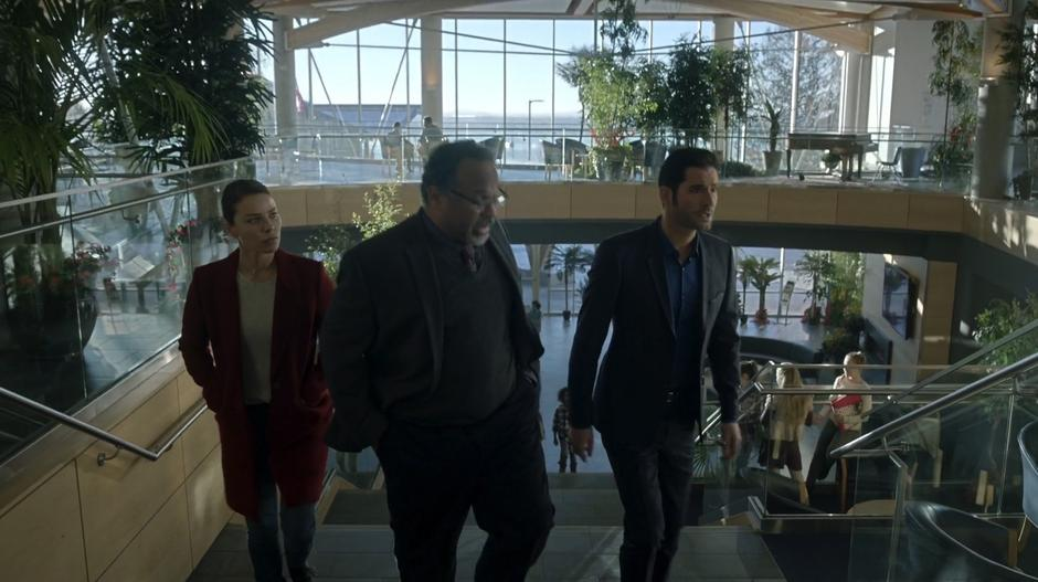 Chloe and Lucifer walk up the stairs with the headmaster while he tells them about the school.