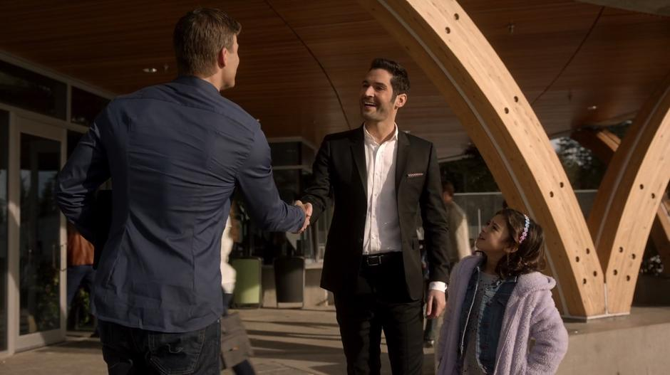 Lucifer shakes Mr. Taylor's hand out front of the school while presenting Trixie as his daughter for the tour.