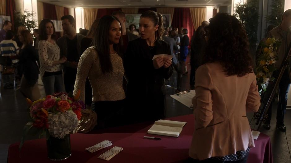 Maze introduces herself as Chloe's wife at the check-in desk while Chloe looks at her with surprise.