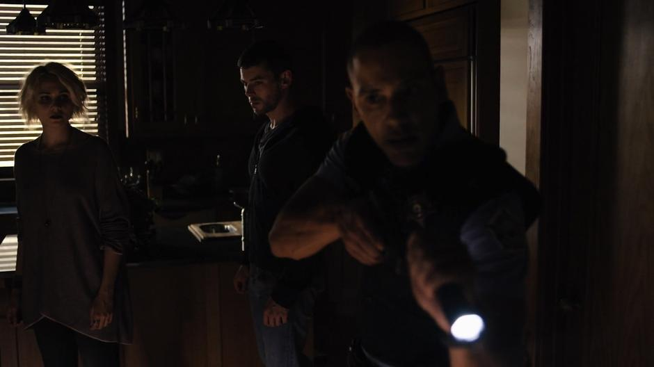 Diego shines his flashlight around the house while Riley and Will follow behind him.