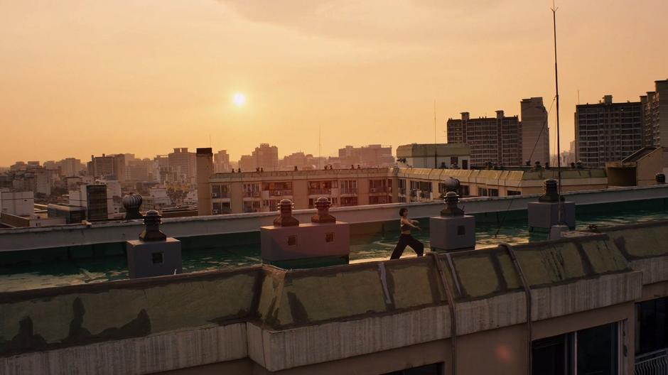 Sun practices on the roof in front of the sunrise.