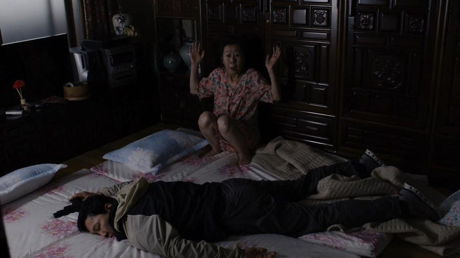 Min-Jung raises her hands to the air as the police officer lies on the ground.