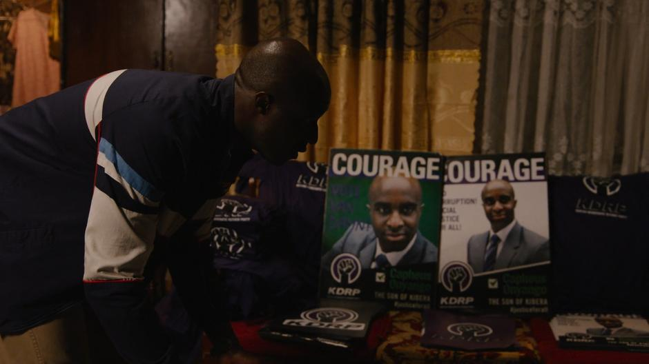 Capheus looks down at the campaign posters and sees his mother asleep on the floor.