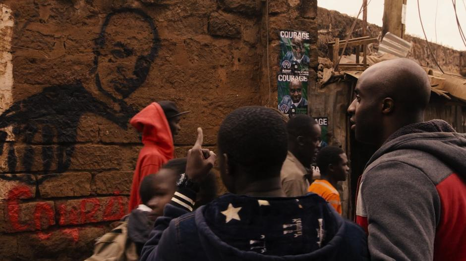 Jela points at the Courage graffiti to Capheus.