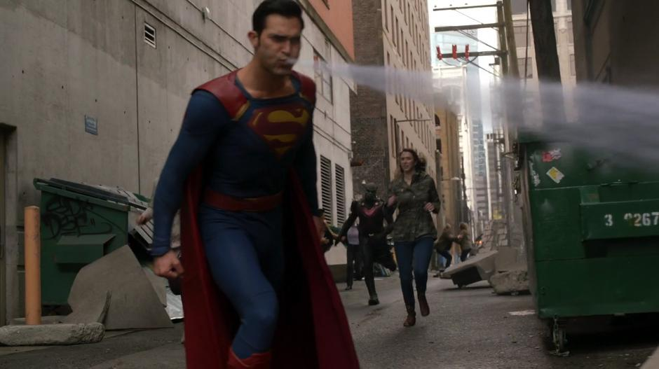Clark uses his freezing breath to fight off some Daxamites while J'onn runs up from the alley.
