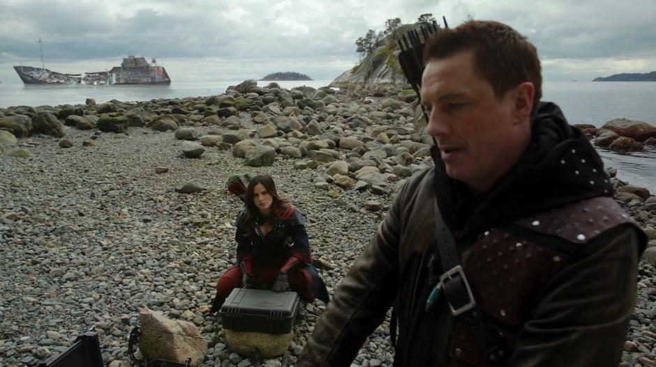 Nyssa prepares some supplies on the beach while talking with Merlyn.