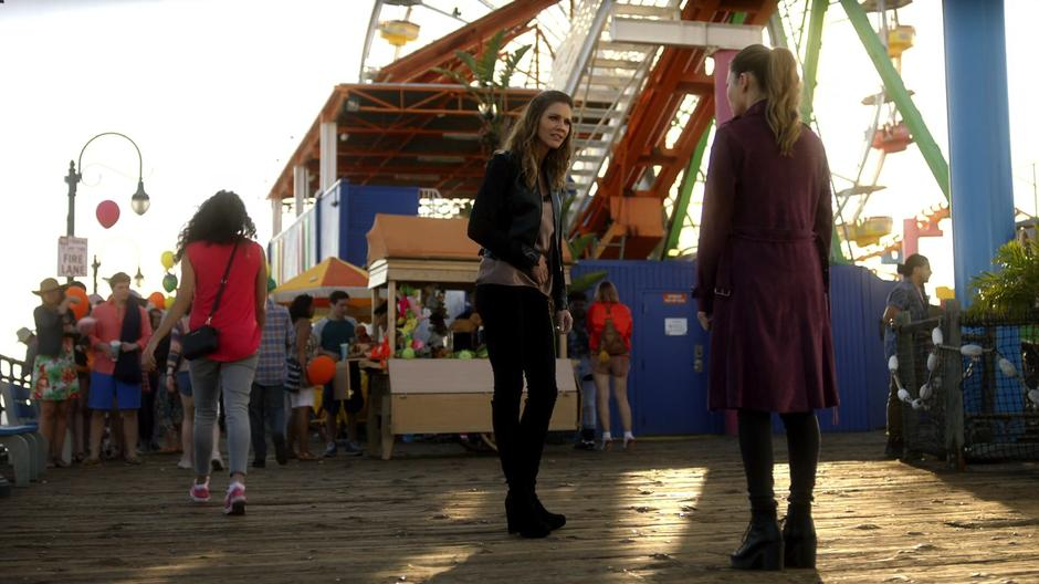 Charlotte talks with Chloe on the pier while holding her old stomach wound.
