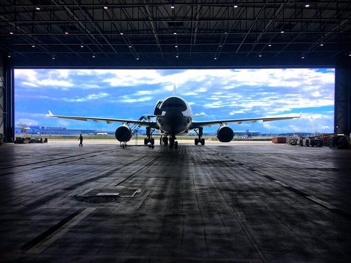 Image of an airplane entering a hangar.