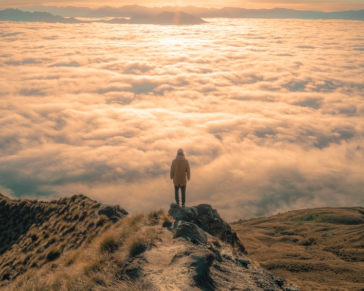 Lone hiker standing on a hilltop overlooking clouds