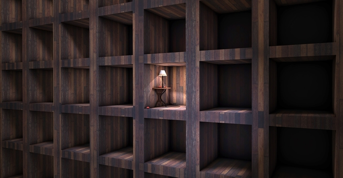 Wooden bookshelf with light from one lamp