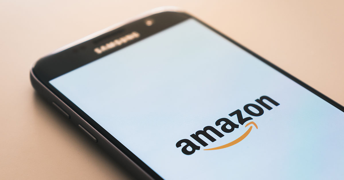Mobile phone on table displaying Amazon shopping app