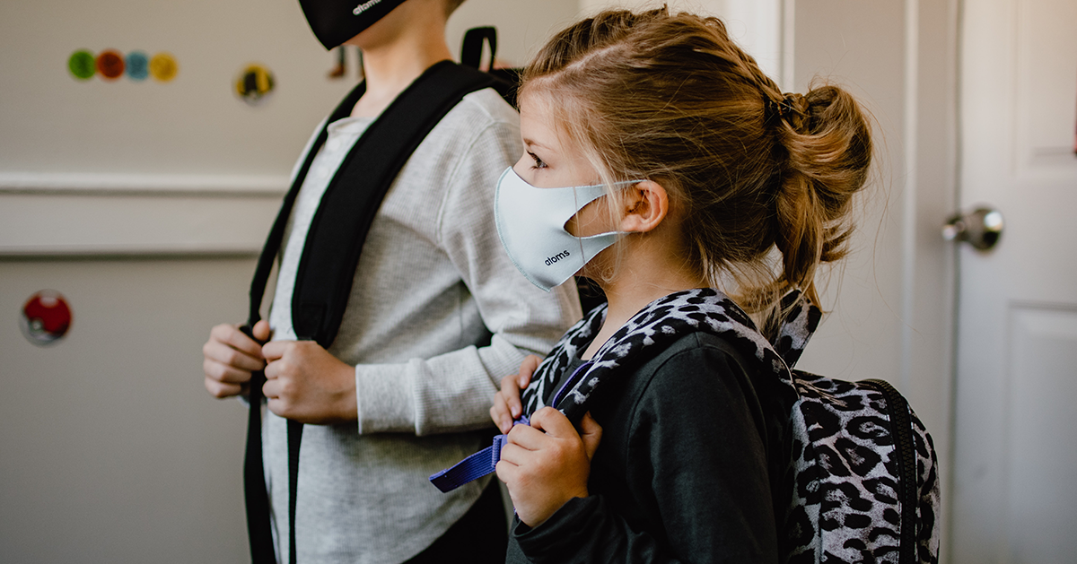 Boy and girl wearing masks and backpacks on their way to school