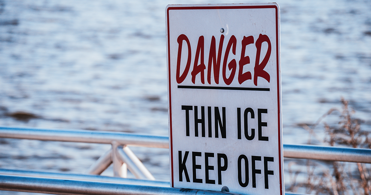 Danger Thin Ice Keep Off sign on dock at lake