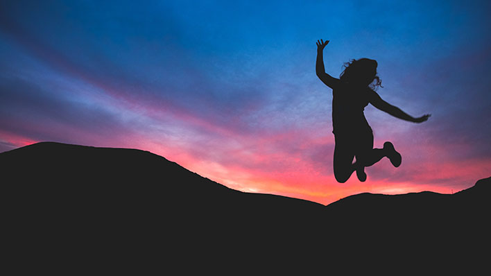 Woman jumping in air with sunset and mountains as a backdrop