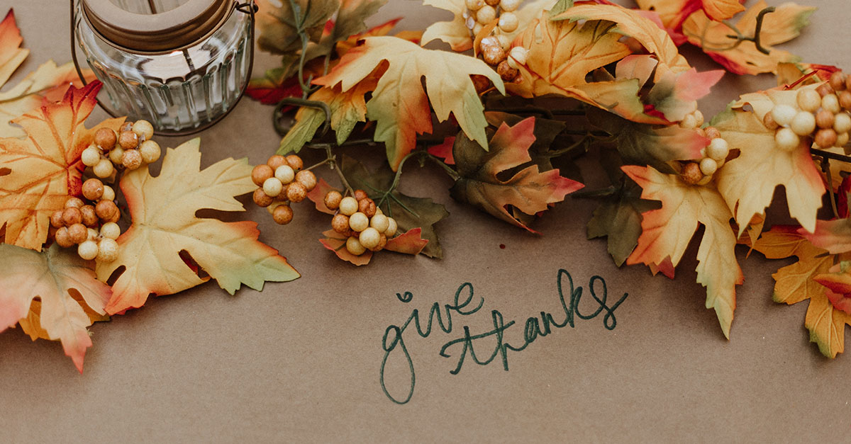 Holiday table setting with leaves, candle, and handwritten text