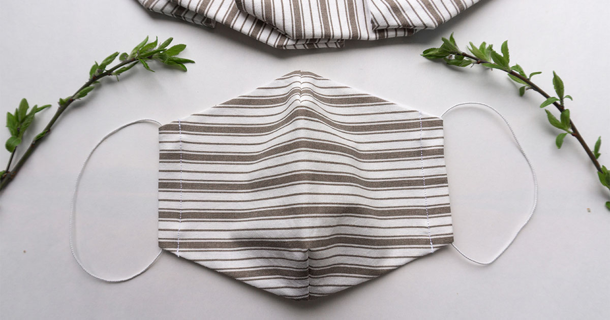 Handmade cloth face mask with striped pattern on white surface