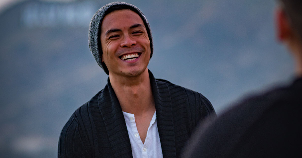 Smiling guy wearing beanie, sweater and henley tee