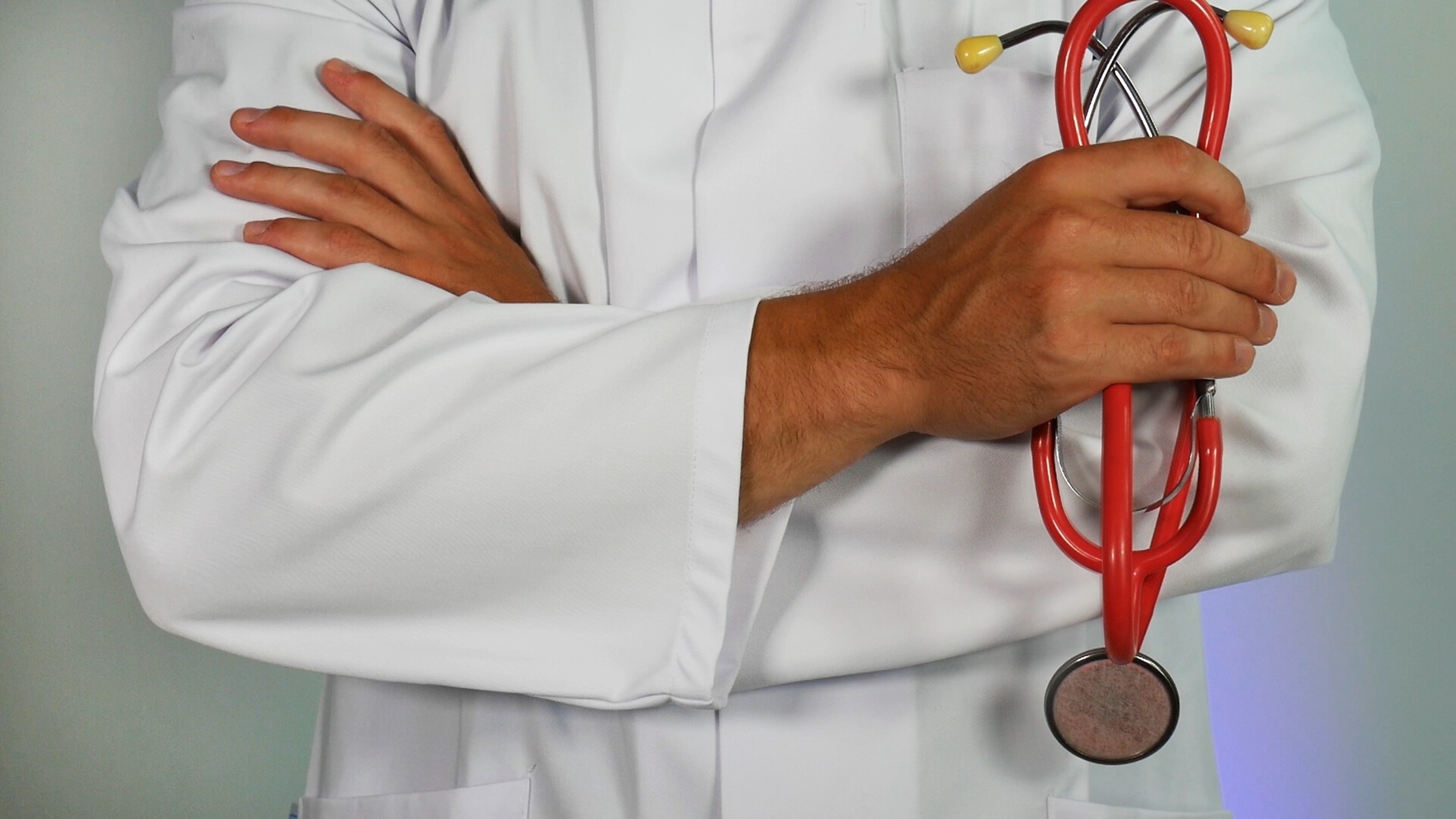 Male doctor wearing white lab coat holding red stethoscope
