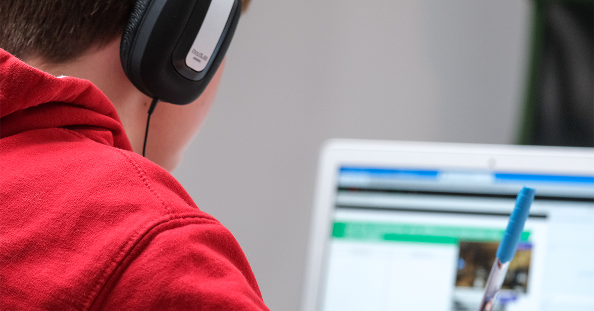 Boy wearing headphones while learning online